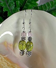The delicate pink clear glass cube that is atop the antiqued silver rose give the hint of that classic flower that is the symbol of love.  The lime green oval focal glass be symbolizes the pale veins
