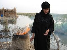 CHEBAISH, IRAQ: Um Karar burns reads in clay oven to make bread. The area of southeastern Iraq has been home to Marsh Arabs for thousands of years, but from the 1950s to the 1990s the marshes were drained leaving environmental and social devastation. After the American led invasion in 2003, parts of the marshes were re-flooded which has led to a small and partial recovery. 2012