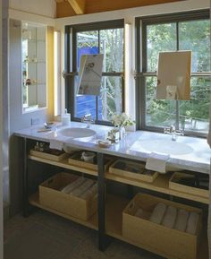 Mirrors mounted over the windows for dual marble sinks
