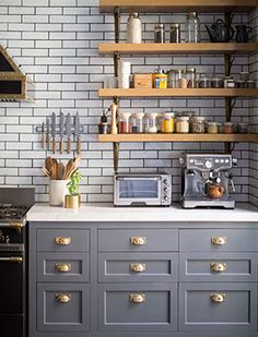 Gray kitchen cabinets, brass fixtures, French oven, vintage style appliances, subway tile.