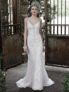 Maggie Sottero - MIELA, Glamorous Swarovski crystals; shimmering pearls; sparkling sequins drift down the tulle and lace skirt of this sheath wedding dress; accented with V-neckline and dainty; pearl encrusted spaghetti straps. Finished with plunging scoop back and pearl buttons over zipper closure.