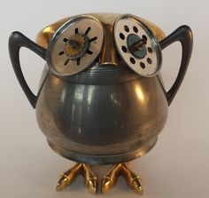 Found Object Robot Owl - This sweet little Robo Owl is made of a pewter sugar bowl, cookie press discs and clock gears for eyes, and brass parts from a vintage transistor owl radio make up his feet and head. He stands 5 inches tall.