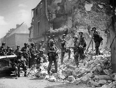 Paratroopers of the 101st Airborne Division standing on the ruins of a house after the Battle of Carentan, july 1944.