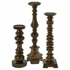 """These mango wood candleholders showcase turned silhouettes, offering classic appeal as a dining table centerpiece or displayed on your hall console table.   Product: Small, medium, and large candleholderConstruction Material: Mango wood and ironColor: Old oakAccommodates: (1) Candle each - not includedDimensions: Small: 14"""" H x 5"""" DiameterMedium: 18"""" H x 5"""" DiameterLarge: 21.75"""" H x 5"""" Diameter"""