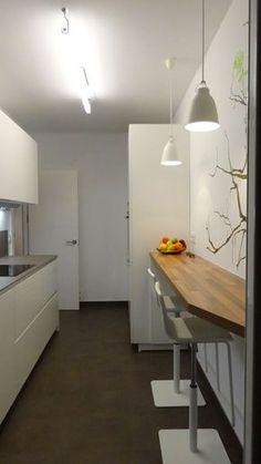 Una cocina alargada también puede tener una barra con sillas altas. Proyecto de Santos Estudio Bilbao #cocinaspequeñasalargadas