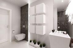 Naturalny szary kamień położony w strefie toaletowej i pod prysznicem uszlachetnia nowoczesny wystrój tej łazienki. Kubiczna wolno stojąca umywalka harmonizuje z kształtem miski sedesowej i małymi szafkami-schowkami zawieszonymi na ścianie. Dla przełamania prostych form przy lustrze zawieszono fantazyjną lampę-pióropusz.