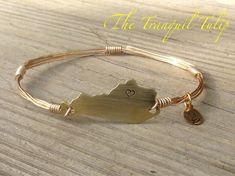 What do you get when you combine one of the trendy wire wrapped bangle bracelets with hand stamped Kentucky pride jewelry? Maybe something like this! A heart is hand stamped onto a brass-gold Kentucky shape, then the shape is wrapped with wire to form a bangle bracelet. This is a finished item and ready to ship out to your home to live on your pretty wrist. The Kentucky shape is made from brass and so is the wire. Check out my other items here in my Etsy store and follow me on Facebook…