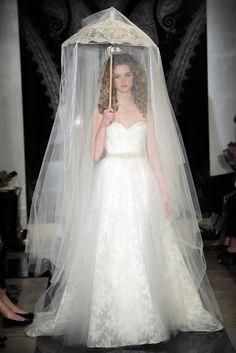 A modelo desfila um modelo de véu de noiva de Reem Acra da coleção 2014, por cima de uma sombrinha