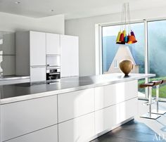 A modern, white kitchen features stainless-steel countertops and a cluster of pendant lights by Hüttners.
