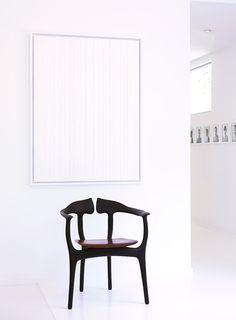 Single chair underneath white artwork
