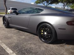 Aston Martin DB9, wrapped in 3M matte dark grey vinyl, 35% tint on the windows, smoked taillights and reflectors, and custom painted rims and break calipers.