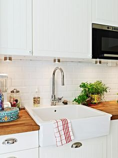 Ikea kitchen. White craftsman cabinets, butcher block counters, apron front sink, stainless steel appliances