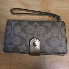 Coach Signature Khaki & Gold Phone Klutch NWT Coach Signature Khaki & Gold Phone Klutch NWT. BRAND NEW! I'm used to a larger wallet and can't consolidate so I'm selling. Just purchased last week while out of town but there is not a coach store near me to return it. Bundle Discount Coach Bags Clutches & Wristlets
