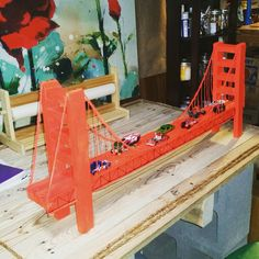 Golden Gate Bridge model with wood and spray paint from Home Depot, yarn and Hot Wheels tracks for the Hot Wheel cars!
