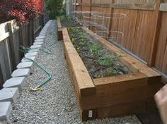 Railroad ties along fence for plants. Great space-saving idea.