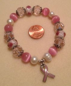 Breast Cancer awareness stretch bracelet.  Features lampwork, cats eye, glass, and freshwater pearl beads, as well as a breast cancer awareness ribbon $25