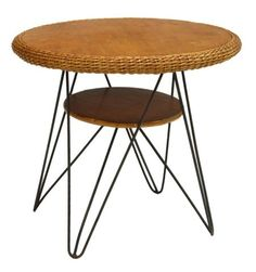 """Mid-century modern wicker and iron occasional table, the round wooden top with wicker edge above small circular shelf, rising on four iron hairpin legs, 24""""h, 26"""" diam Start Price: $80.00"""
