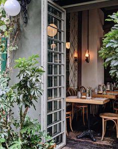 indoor outdoor dining area at lardo restaurant in mexico city. Outdoor Dining, Dining Area, Indoor Outdoor, Storefront Signage, Black Bucket Hat, Plant Table, Mexico City, Greenery, Outdoor Structures