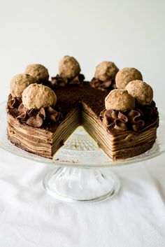 tiramisu crepe cake; thin french crepes are brushed with espresso syrup layered with tiramisu cocoa sweet mascarpone frosting and topped with dark truffles
