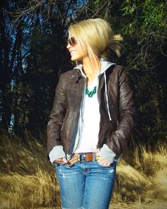 Hoodie/sweater layered under a leather jacket. Belt and necklaces make this.