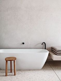 White concrete walls and light-colored terrazzo floors for a calming bathroom look. Terrazzo inspiration for home interiors and redecoration ideas.