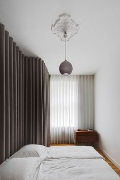 Dark grey curtains and metallic fixtures have been used to update an apartment in the Berlin's Mitte district