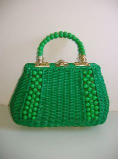 1950's plastic coated straw purse in emerald green with beaded handle. To accompany a red and white candy striped summer blouse and full orange skirt with cinched in waist and poofy petticoats, featuring line drawings of Paris in the 50's around the hemline.  Accessorise with perky acrylic fruit emblem jewellery to accentuate the bag and the skirt.