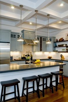 Traditional Kitchen with Inset cabinets, Coffered ceiling, Soapstone counters, Painted wood panel wall, Breakfast bar