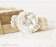 This is a tea dyed headband  with a handmade vintage lace,  and fabric flower complete  with a jewel center ~  $13.50