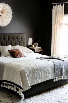 Black walls in the bedroom satisfied Morse's desire for drama and sophistication, but light bedding, curtains, and accessories (like that an eye-catching lamp) combat any dreariness.   - HouseBeautiful.com
