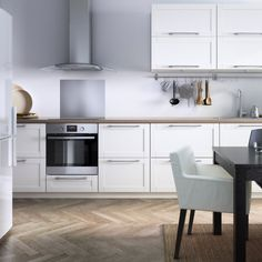 Modern white eat-in IKEA kitchen with stainless steel appliances