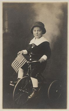 Boy on a Tricycle with an American flag