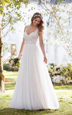 Soft, romantic, and light-as-air, this boho wedding dress from Stella York was made for the laidback, casually-cool bride. The bodice of this French tulle over matte-side Lavish satin gown is constructed of double organza, giving the appearance of sheerness. Adorned with lace swirls and beading, it is the perfect complement to the tulle, A-line skirt.