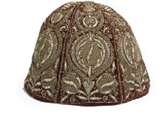 """A """"CROMWELLIAN"""" GENTLEMAN'S NIGHT CAP  17TH CENTURY  Of red velvet embroidered in metal threads with pomegranates and embellished with spangles, with inscribed tag: """"This cap belonged to Major Buntine, uncle of William Baillie of Monkton. He served under General Lesley in the Civil Wars; and particularly distinguished [sic] at Philiphaugh. Cromwell made him Master of the Horse in Scotland. Monk sent him to Breda to see Charles II"""" 7 in. (18 cm.) high; 11 in. (28 cm.) diam."""