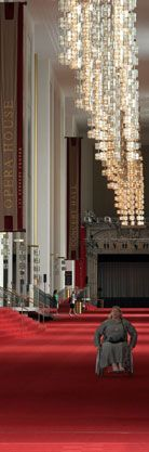 """A woman in a wheelchair coming down the Grand Foyer in the Kennedy Center.  The Foyer has bright red carpeting, gold and glass chandeliers, and two large banners reading """"Opera House"""" and """"Concert Hall"""" are visible on the left."""