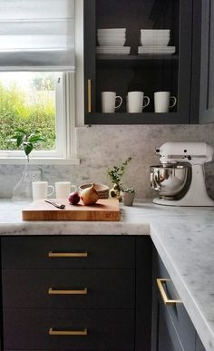 Dark gray kitchen cabinets adorning long brushed brass pulls are topped with a thick marble countertop positioned against a marble slab backsplash and beneath a glass front cabinet fixed beside a window covered in a white roman shade.