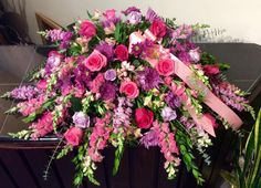 A very feminine casket spray, jammed pack with roses, mums and snap dragons.