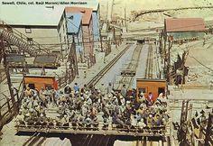 Sewell. Conjunto de trabajadores abordo de un ascensor de carga, subiendo hacia la cima de la ciudad.