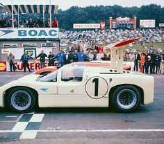 """Waiting for the green flag at the BOAC 500 at Brands Hatch, Mike Spence in the 2F sits alongside John Surtees' Lola T70 Coupe. Denny Hulme's Lola T70 Coupe is on the far end. All cars were required to display the BOAC """"speedbird"""" sticker on both sides of the car. No other sponsorship decals were permitted. Max LeGrand Photo (repaired)."""