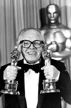 Lord Richard Attenborough, who served with the Royal Air Force before embarking on his film career, pictured holding two of his Oscars for best film and best director for Gandhi.