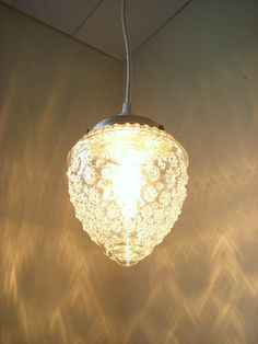 Perfect pressed glass pendant to light your space. Crisp clean clear glass with texture. Resembles a raspberry or acorn. Compliments any decor style. Would fit perfectly over the kitchen table or in the corner of any room for accent or reading light. *This hanging lamp comes with a brand