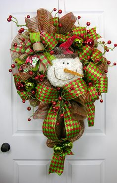 A snowman wreath with large loops of red/lime green harlequin ribbon. This is a large premium red/lime green striped deco mesh wreath with spiral glitter ball stems. There are double loops of ribbon a
