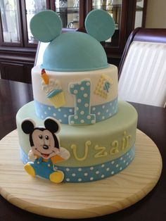 "Mickey Baby Cake - Mickey cake is made entirely of marshmallow fondant. Mickey and #1 backing made of white gumpaste. 6"" hat cake, 8"" tier, and 12"" tier. Fabric ribbon."