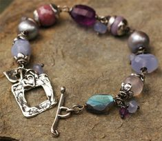 A Beautiful Soul.... Violet is the color of spirituality Amethyst, the stone of transformation. This piece abounds in little amethyst dangles all around it as well as a larger stone. This treasure trove includes- chalcedony, Labradorite, Pink Sapphire and Freshwater Pearls.  Bracelet length is........7.0 inches Will fit a wrist size 6. to 6.5