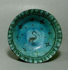 coupe à l'ibis sur piédouche, en céramique bleu turquoise à décor peint en noir, d'un ibis au centre et d'une frise épigraphique en caractères coufiques sur le marli.  Double bande noire parallèle sur le bord externe.  Iran (Nishapour) 13è siècle  Diam.19.5 cm