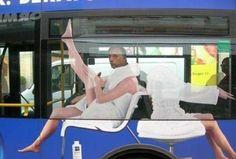 Hombre sentado en autobús con publicidad femenina sobre el