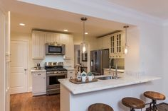 Transitional Kitchen with Hardwood floors, Inset cabinets, Breakfast bar, Undermount Sink, Complex marble counters, U-shaped