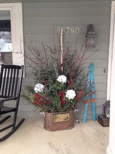 Spruce tops, red berries, hydrangeas in a copper boiler for the front porch! Add the children's blue skis for a pop of color!