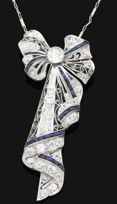 A Belle Epoque sapphire & diamond pendant/brooch, ca 1918.  The pendant/brooch modelled as a stylized bow, set with a central old brilliant-cut diamond, to the pierced diamond-set ribbon mount, accented by french-cut sapphires, with fine-link neckchain, pendant/brooch mounted in platinum, chain mounted in 14 ct white gold, central diamond weighing approx 0.60 ct, remaining diamonds approx 1.50 cts total, pendant/brooch length 6.5cm, chain length by amelia