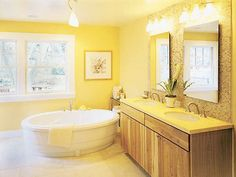This bathroom has a lot of yellow in it with the walls to the counters to the tiling on the wall making it monochromatic.